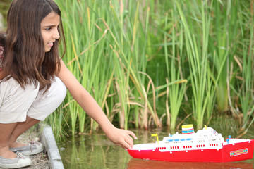 Girl playing with a toy boat on a lake