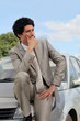 Businessman thinking by his car