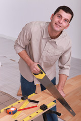 Man sawing wooden floorboards