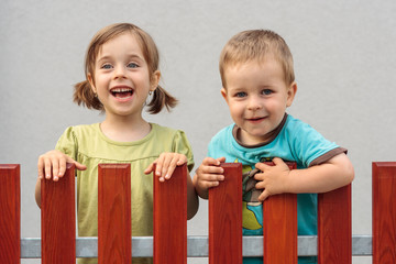 Brother and sister smiling behind the fence