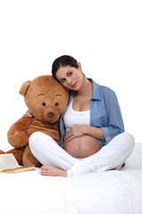 Pregnant woman embracing a teddy bear