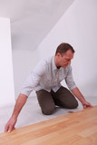 Man installing wooden flooring