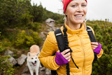 Fototapety Happy woman hiking in mountains with akita dog, Poland