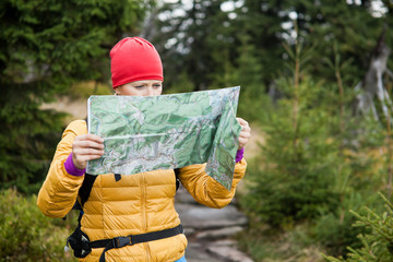 Woman hiking and reading map in forest