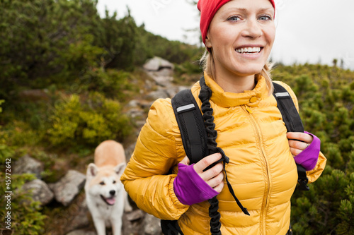 Happy woman hiking in mountains with akita dog, Poland