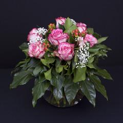 Rosen in runder Glasvase auf Schwarz