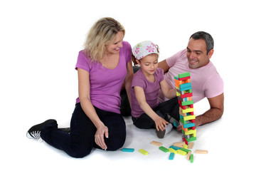 Parents stacking bricks with their daughter