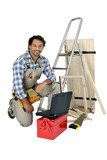 Tradesman posing with his building materials, tools and laptop poster