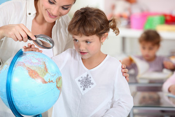 schoolmistress teaching geography with globe