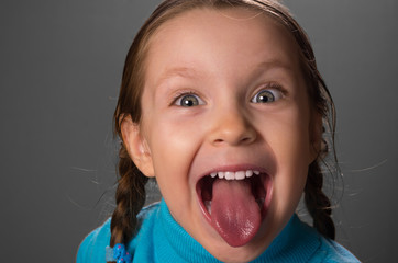 Little girl showing the tongue.