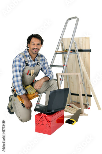 Tradesman posing with his building materials, tools and laptop
