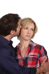 Man whispering in an unhappy woman's ear