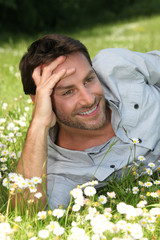 Happy man laid in a field