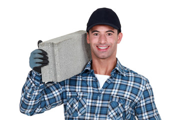 A man carrying a breeze block.