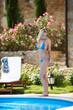 Blonde Frau im Bikini posiert am Pool