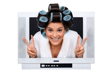 Woman with curlers peering TV screen
