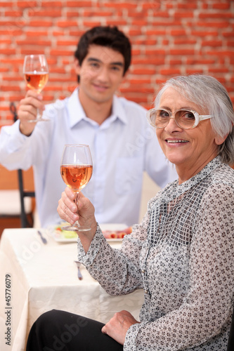 Grandmother and young man drinking rose wine