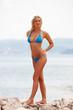 Blonde Frau im Bikini posiert am Strand