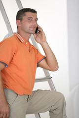 Man making call next to step-ladder
