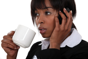 businesswoman drinking coffee and talking on her cell