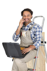 Tradesman typing on his laptop