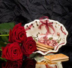 Beautiful porcelain plate with cupcakes and red roses