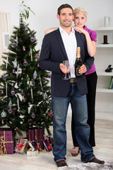 A couple enjoying champagne at Christmas.