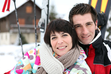 Couple in front of a ski cabin