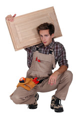 cabinetmaker carrying cupboard door over shoulder