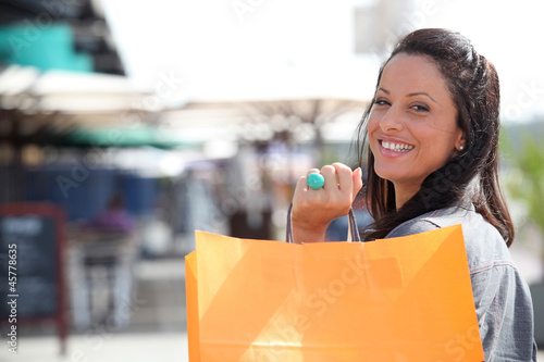 young woman holding a carton bag near a restaurant or a cafe
