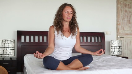 Healthy woman sitting in pose yoga on bed
