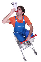 Builder with megaphone sat in shopping trolley