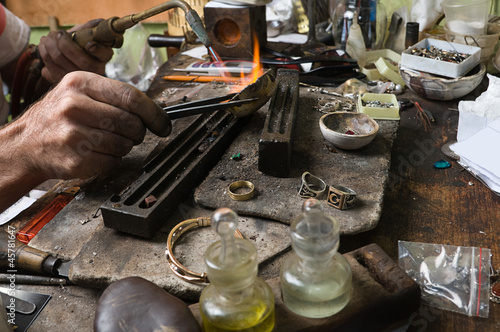 Goldsmith working on an unfinished ring with flaming torch
