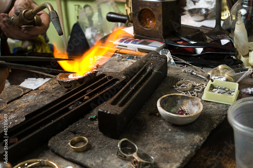 Jeweler melting silver with gasoline burner
