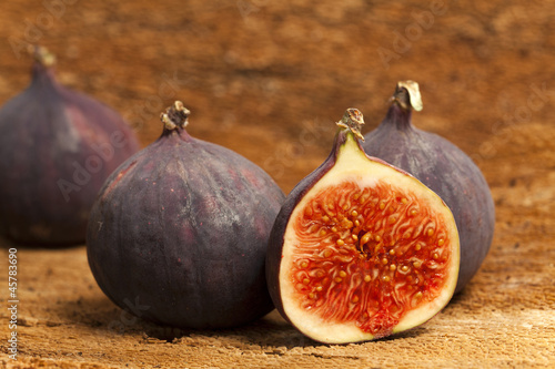 Two whole and a halved fig fruits on bark as background