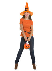 Happy woman holding Halloween bucket with sweets
