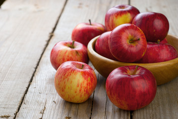 A bowl of red apples on the wooden table