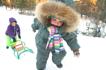 child with sled in winter