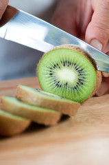 Cutting a kiwi fruit, close-up, studio shot