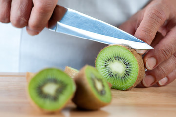 Food preparation - cutting kiwi fruits, studio shot