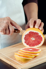 Vertical shot of female hands cutting a grapefruit