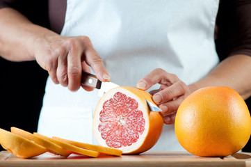 Senior woman cutting a grapefruit, horizontal shot