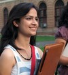 Young Indian / Asian college student holding a file folder.
