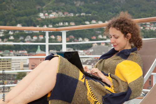 girl in blanket lying on sunbed with laptop on deck ship