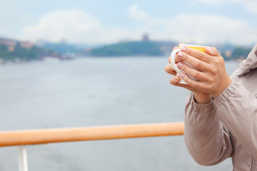 Woman hold cup in hands on deck of ship, focus on cup