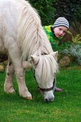 Kind blickt hinterm Pferd hervor