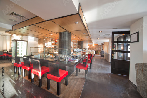 Sushi restaurant  with red chairs and refrigerator, indoor