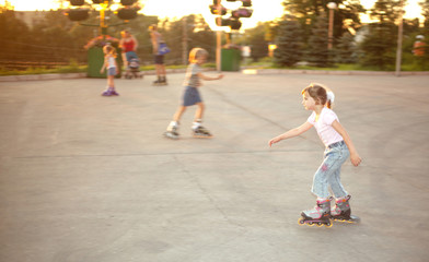 Kids ride on roller skates on skate yard