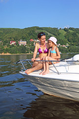 Mother daughter sunbathing and talking on cutter on river