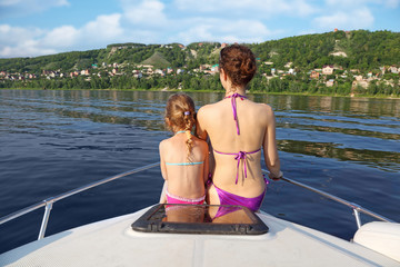 Mother daughter sunbathing and talking on bow of cutter on river